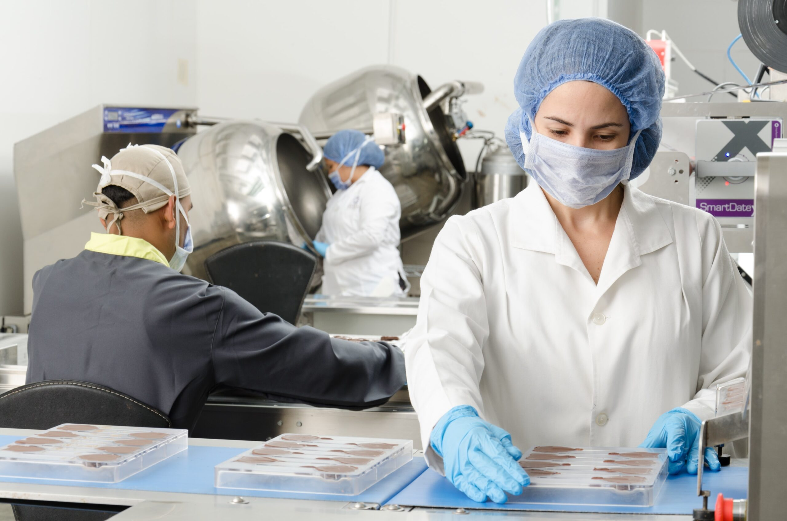 lady-wearing-overall-and-gloves-manufacturing-chocolate-feature-image-for-food-and-beverage-industry-blog