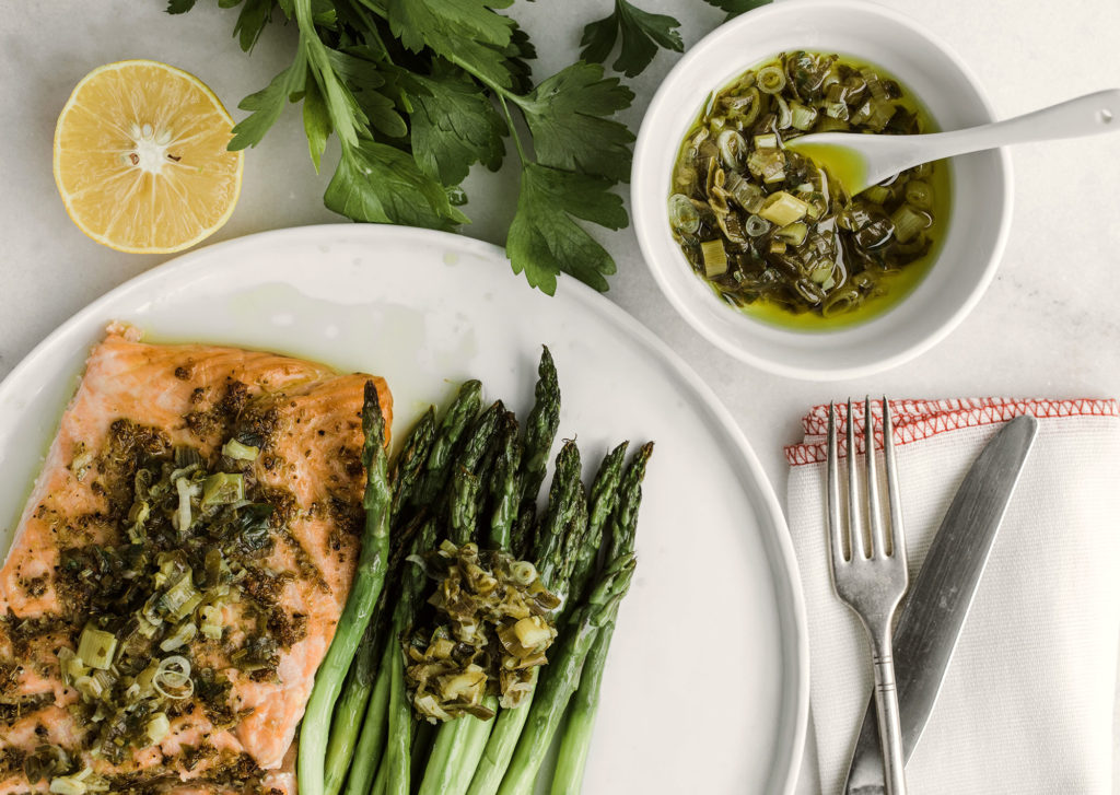 Salmon and asparagus on a plate with a side of scallion sauce