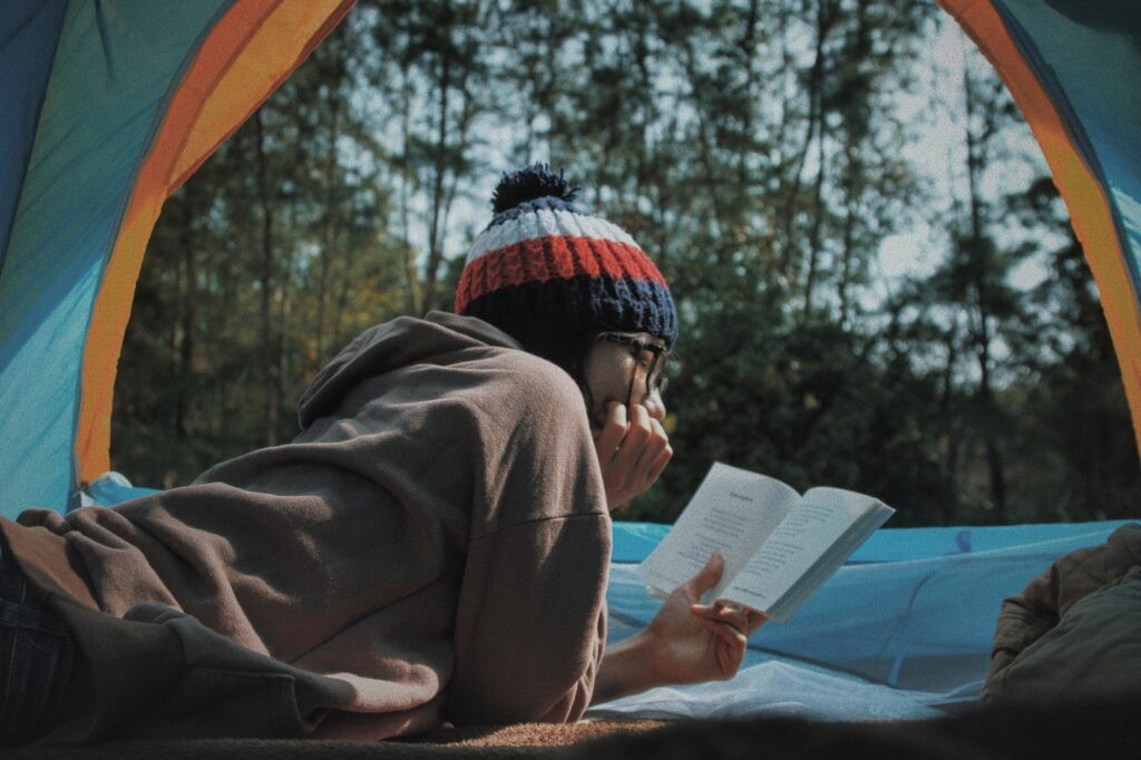 girl reading a book in tent