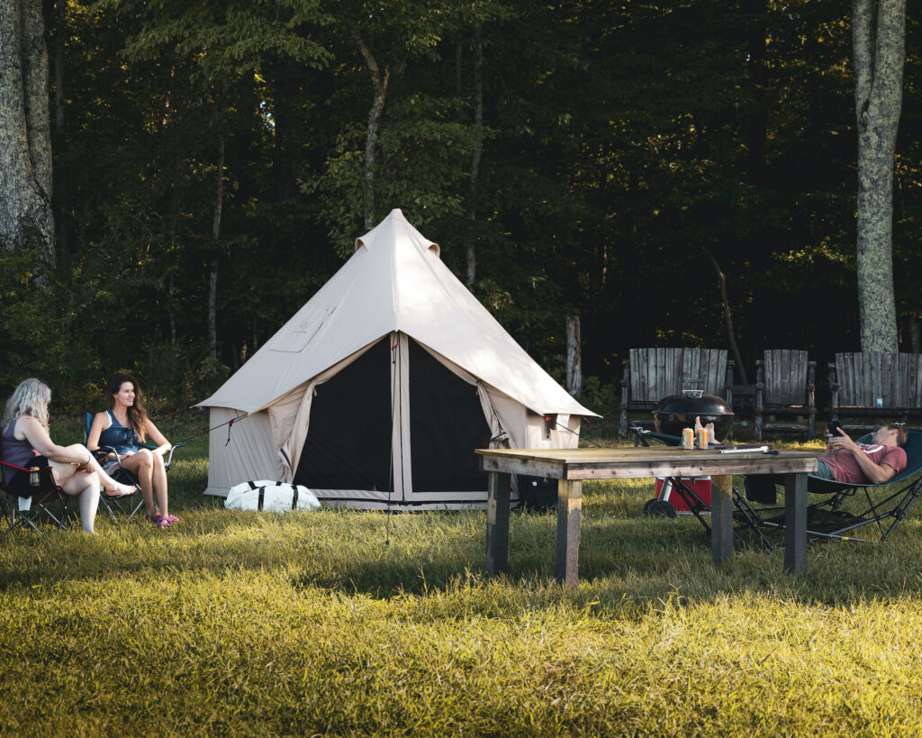 glamping tent outdoors people grass table bell tent canvas tent