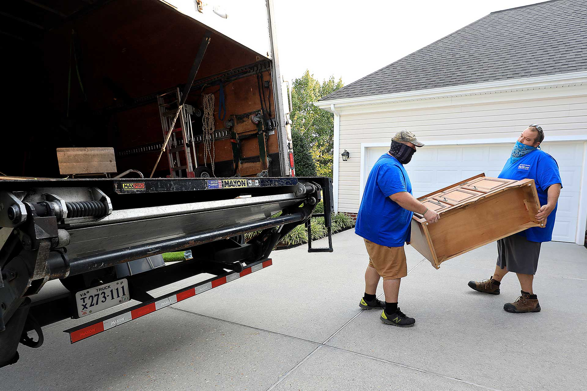 ReStore truck crew Willie Harris and Dustin Hickman land a cabinet into their vehicle Wednesday morning September 24, 2020.