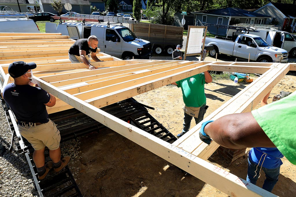 Pre-fabricated framing is unloaded at a Habitat for Humanity home build in Williamsburg
