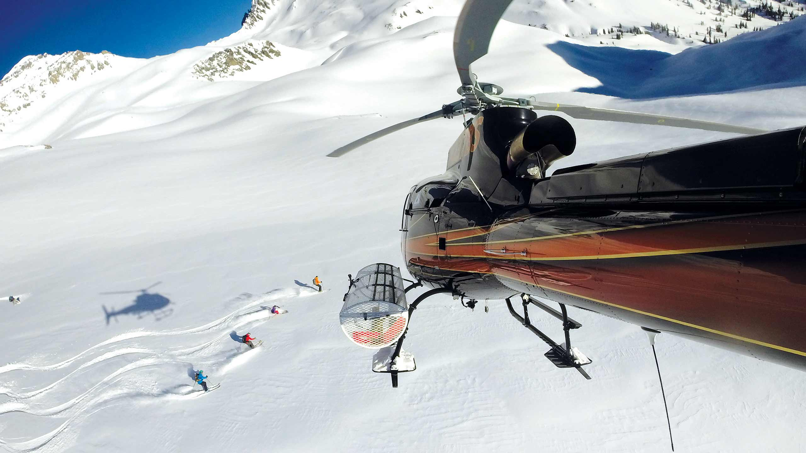 Heli-Ski Group with Helicopter Above