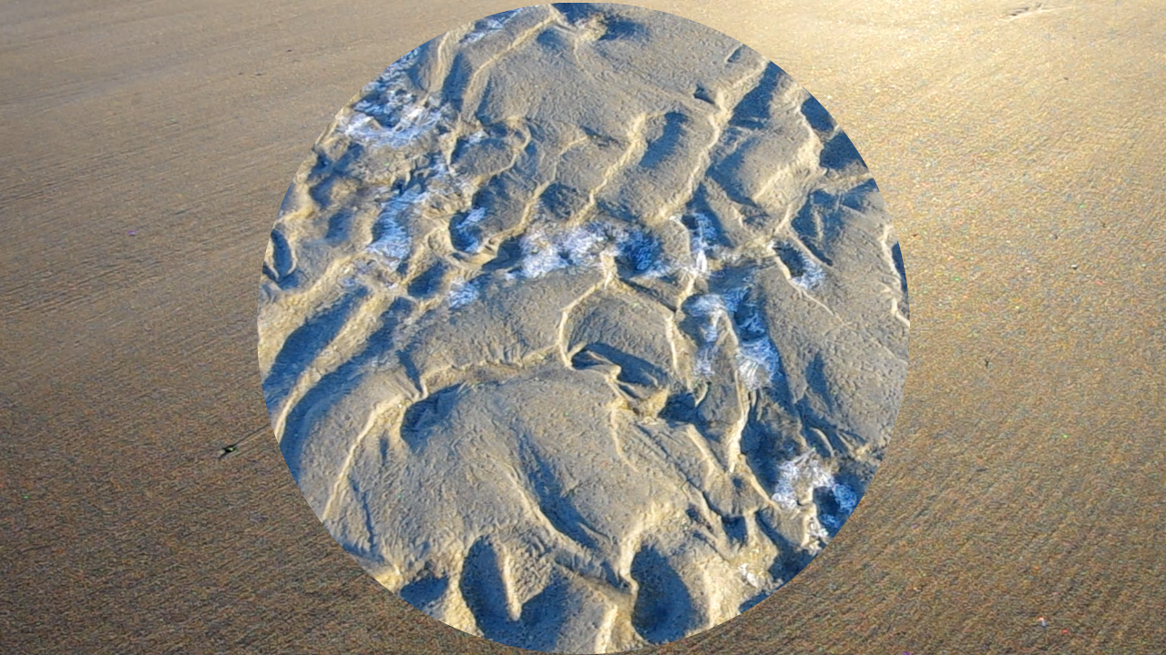A rectangular photo of smooth sand is cut with a circular photo of ridged sand with ice in its nooks.