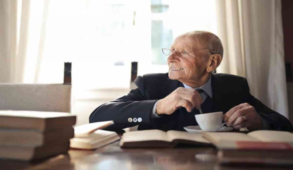 old man smiling with books