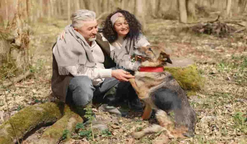 man, woman and dog having a good time