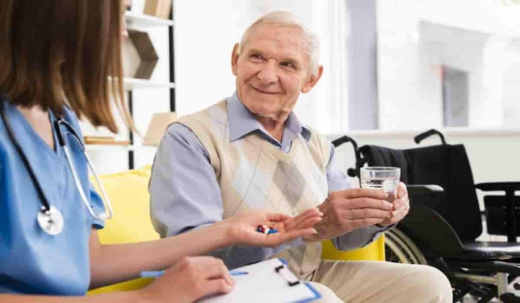old man with doctor taking pills