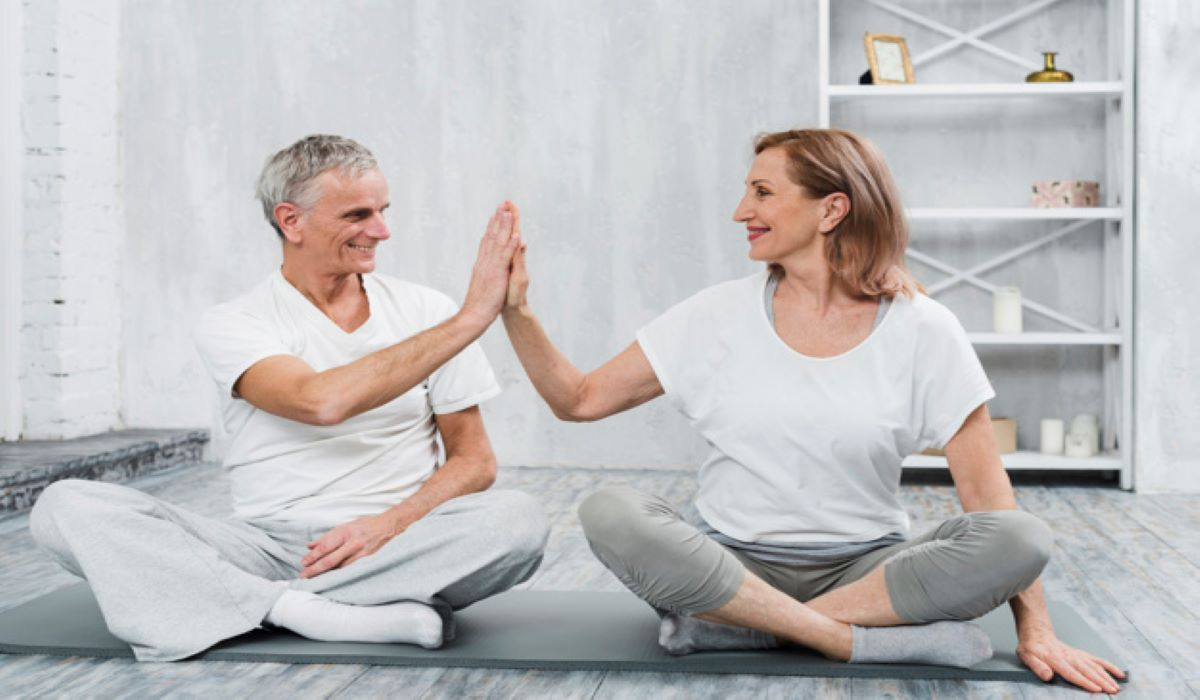 Cheerful old couple doing yoga together