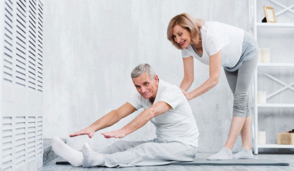 Old couple helping each other in asanas