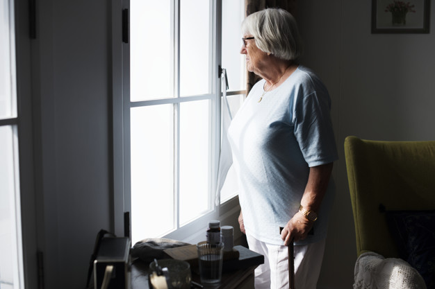 Lonely senior woman looking out of window