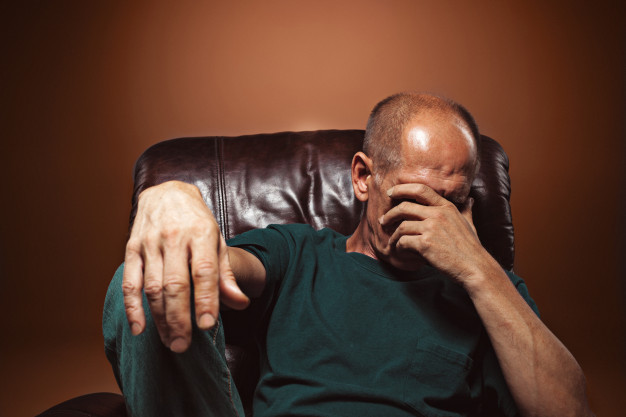Old man holding forehead due to stress