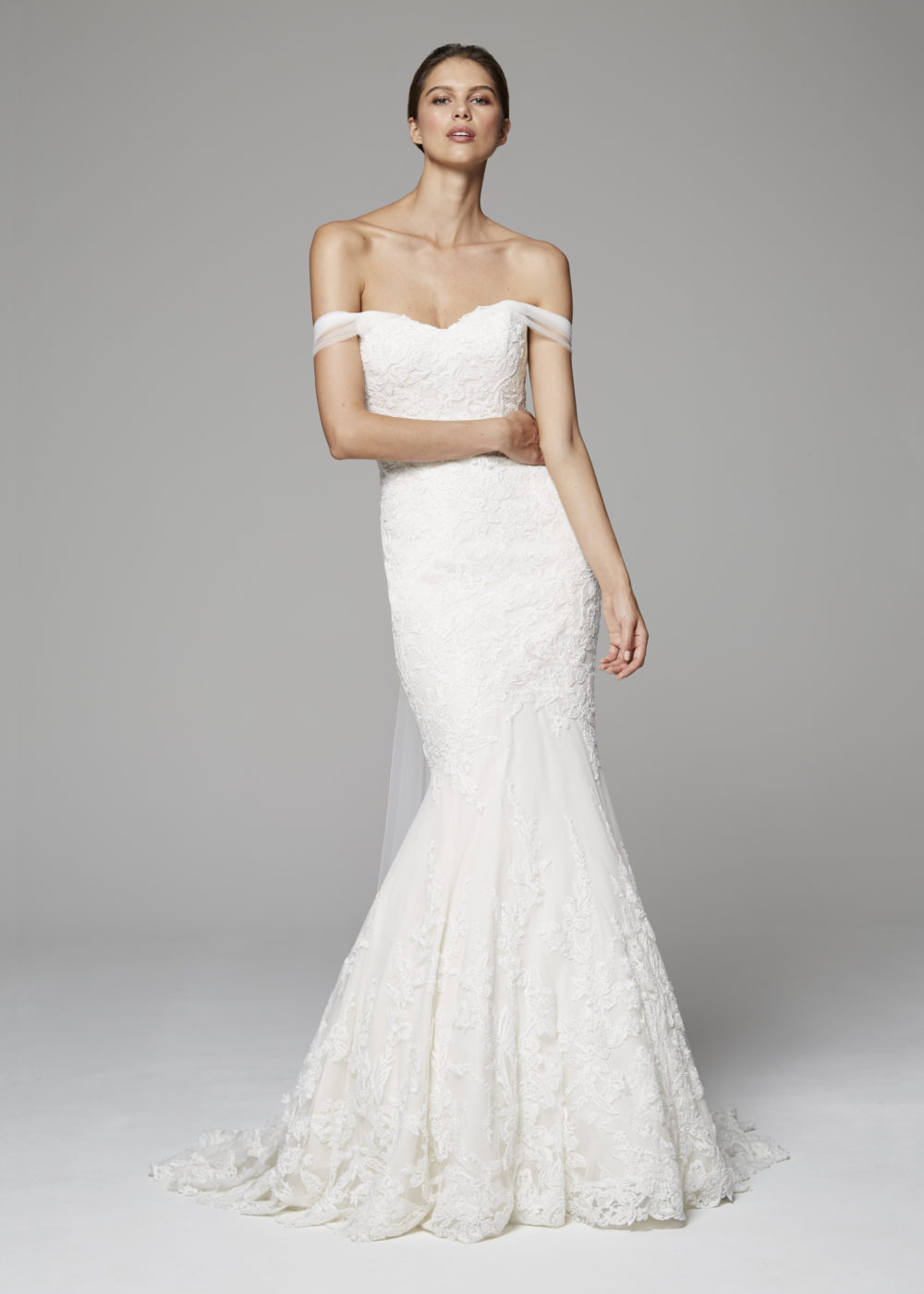 Refined mermaid gown of beaded embroidered lace with tulle off-the-shoulder drape extending to train.