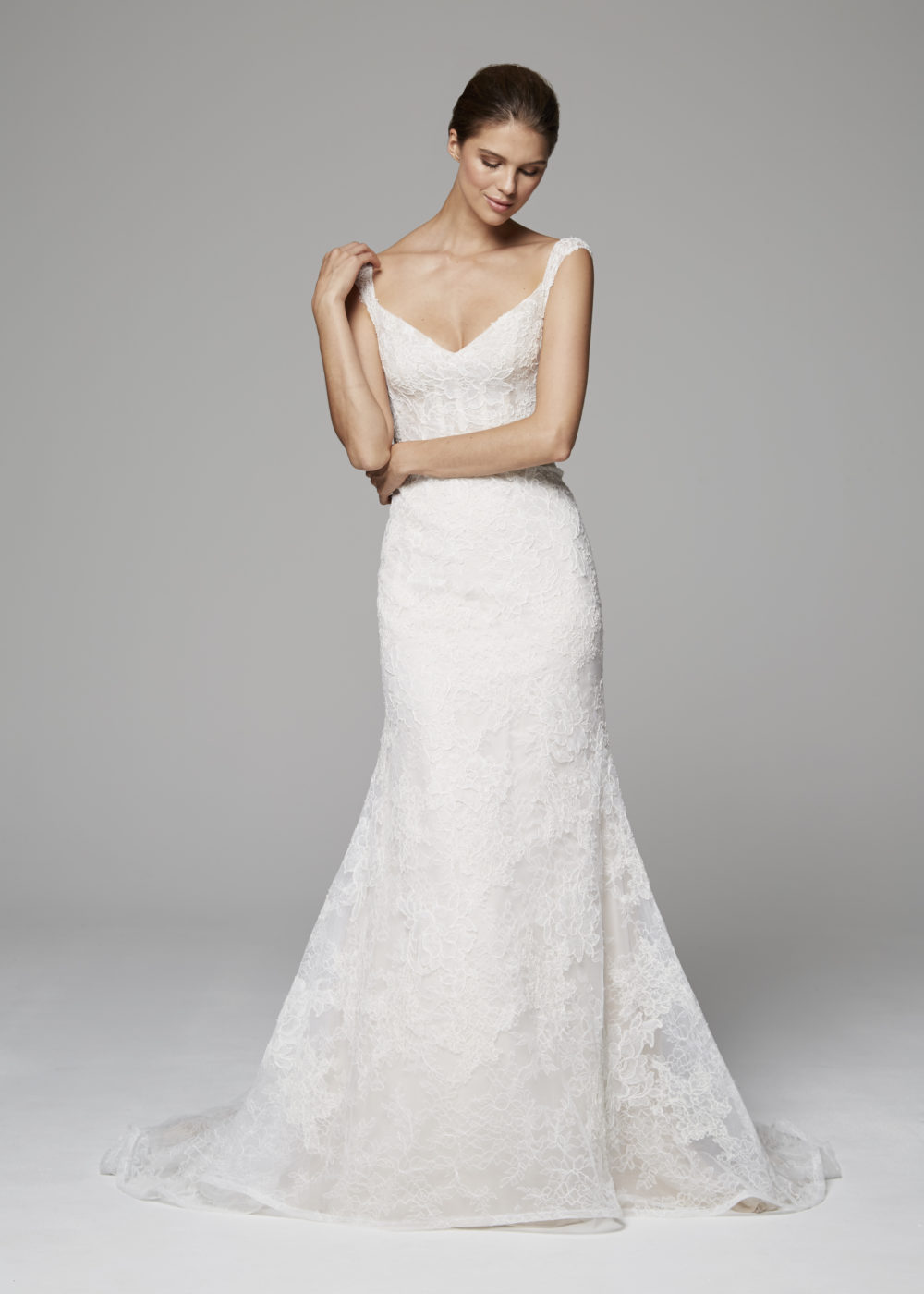 A corseted bodice and off-the-shoulder straps adorned with a collage of French Alençon laces on Chantilly lace.