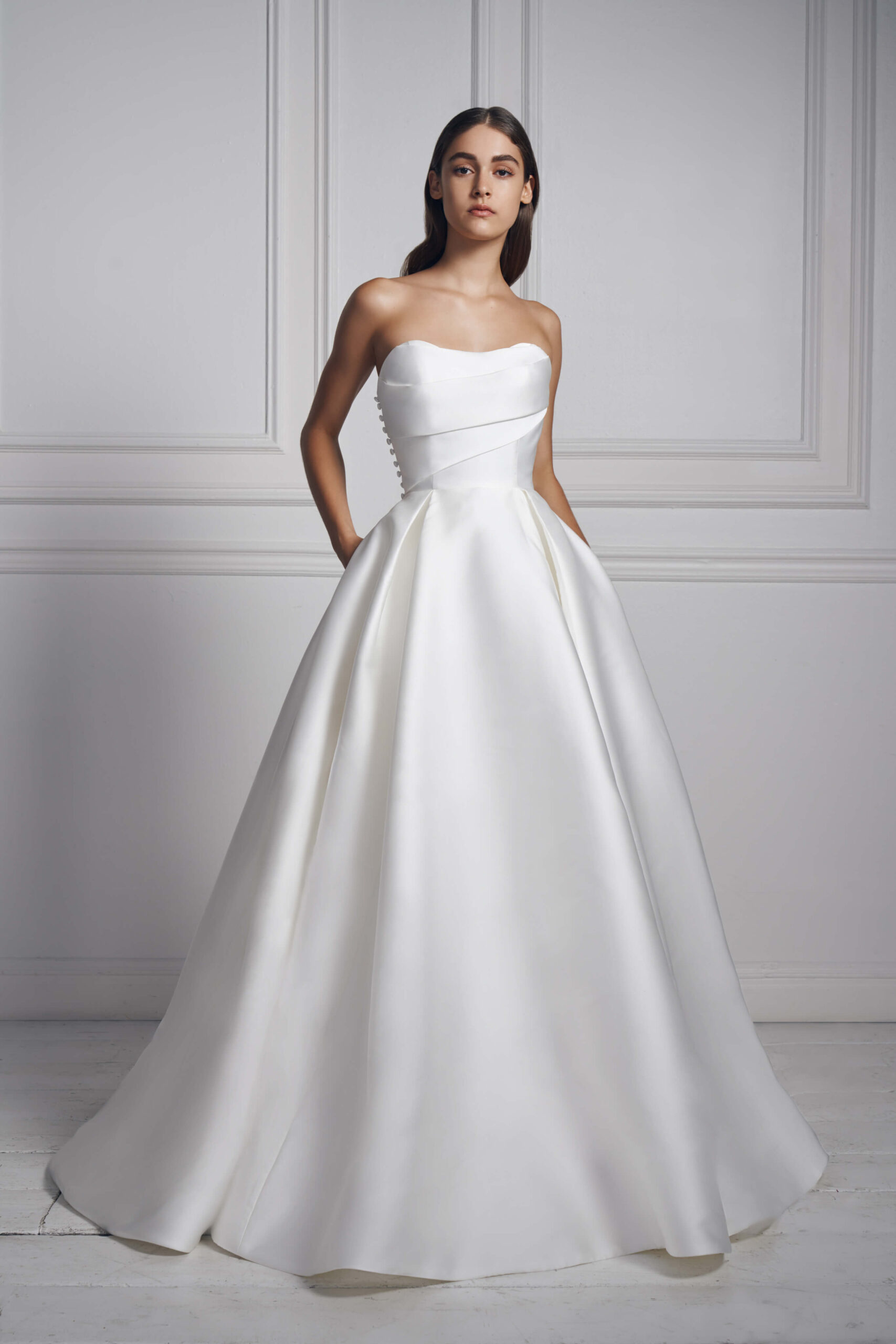 Strapless white silk ball gown by Anne Barge. This classic ball gown is adorned with buttons.