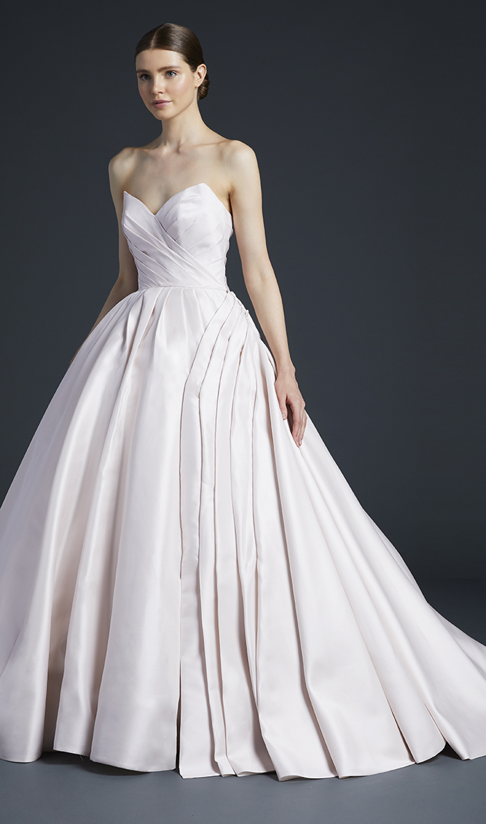 Pointed strapless ballgown composed of Kalika with intricate pleating accented by oversized covered buttons and bound button holes.