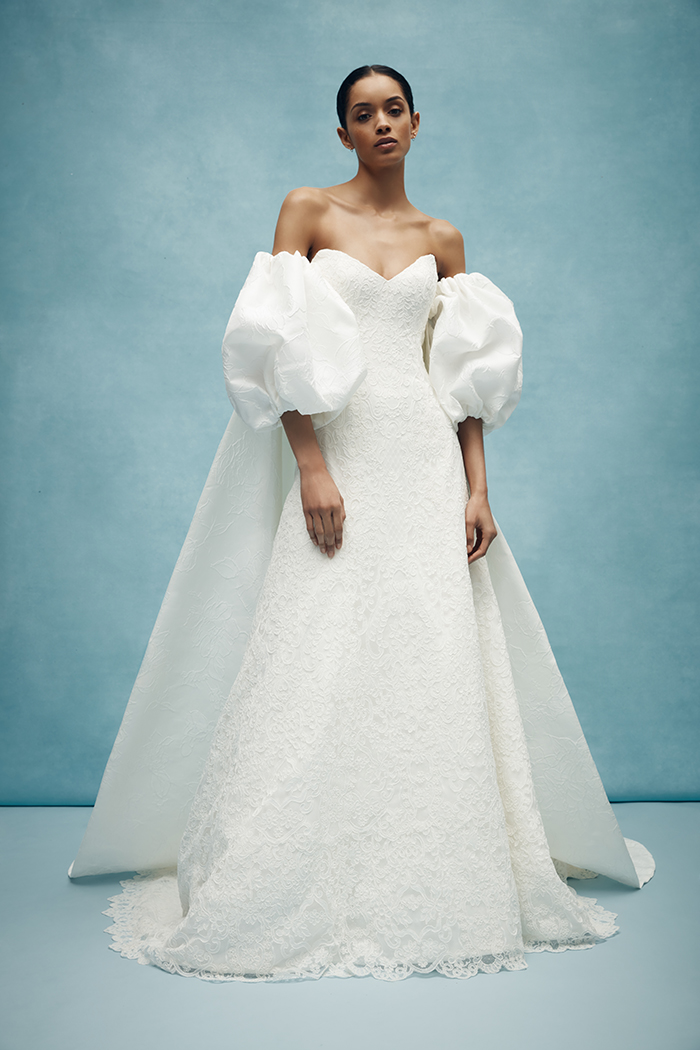 Fall in love with Anne Barge's off the shoulder cape with dramatic puff sleeves of floral embossed jacquard. Contact Sposa Bella For more information