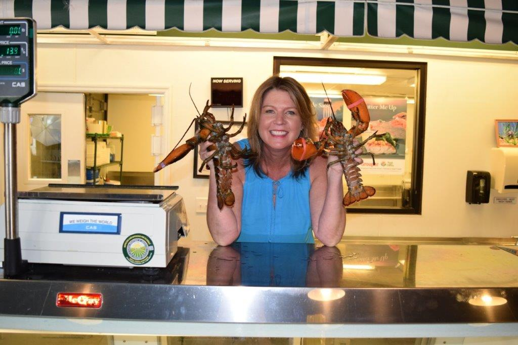 Josee in fish market holding lobsters