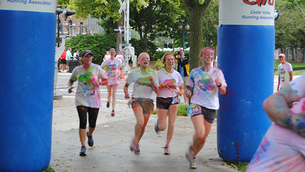 The Crunch Berry Run, runners crossing the finish line covered in color!