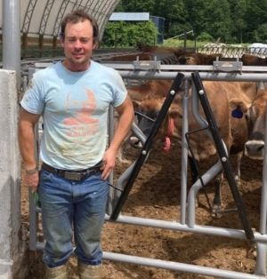 Caleb Smith is standing in the barn yard. A herd of jerseys are in the pen behind him. He is wearing jeans, boots caked in mud, and a light blue tee shirt.