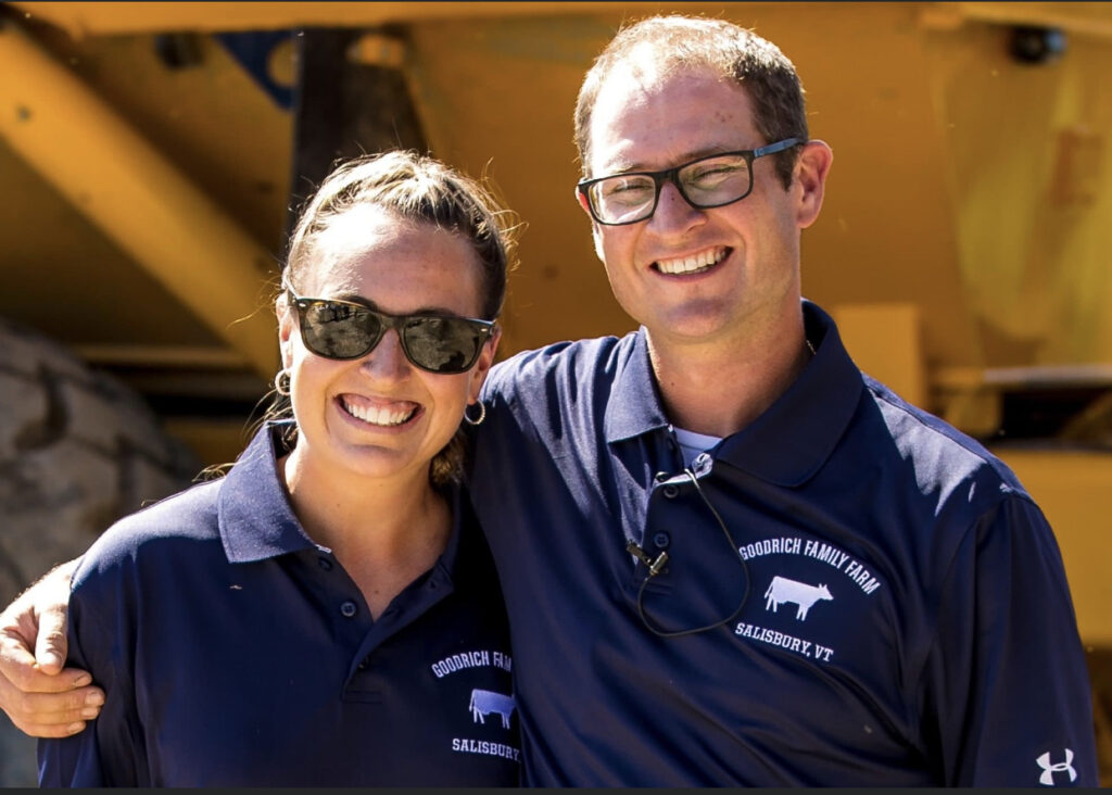 A photo of Danielle Goodrich and Chase Goodrich. Both are wearing navy blue polo shirts emblazoned with their farm's cow logo. They are smiling, and Chase has his arm wrapped around his sister's shoulder.