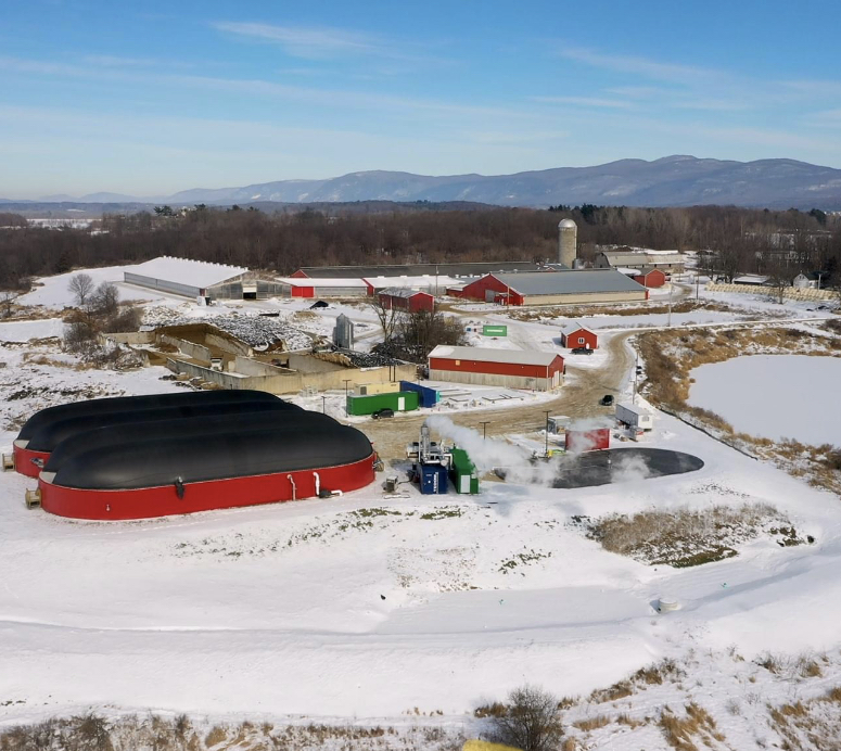 An aerial view of Goodrich Family Farm. The red barns are in the background. The red digester is in the foreground. The ground is covered in snow. Blue skies over the Green Mountains are in the distance.