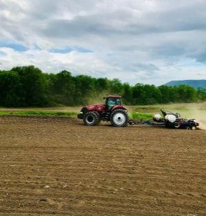 A farmer plants their corn using no-till. A red tractor pulls a no-till corn planter across dark brown soil on an overcast day.
