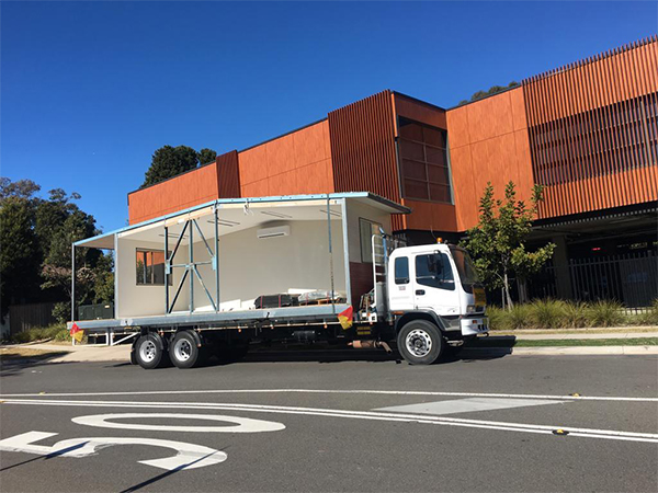 Freight forwarder truck carrying a site shed