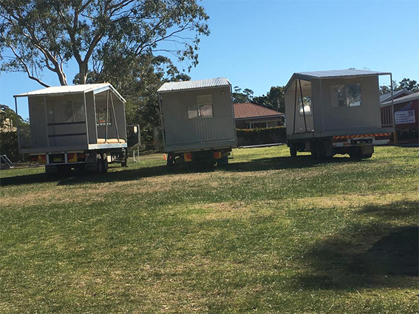 Freight forwarder trucks carrying site sheds