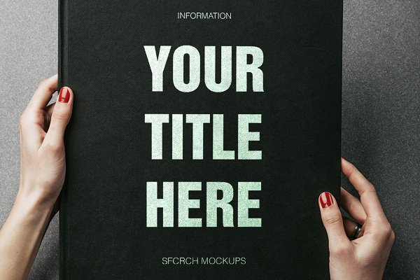 Hands Holding a Big Black Book