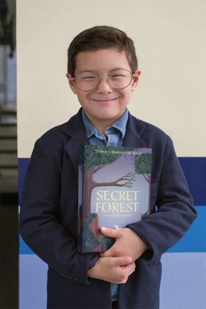 Young Smiling Boy Holding a Book