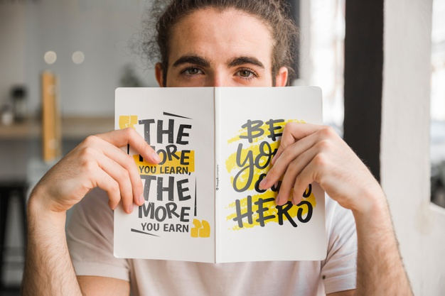 Man Holding Book in Front of His Face