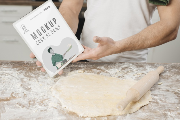 Man Holding Book and Rolling Dough in the Kitchen