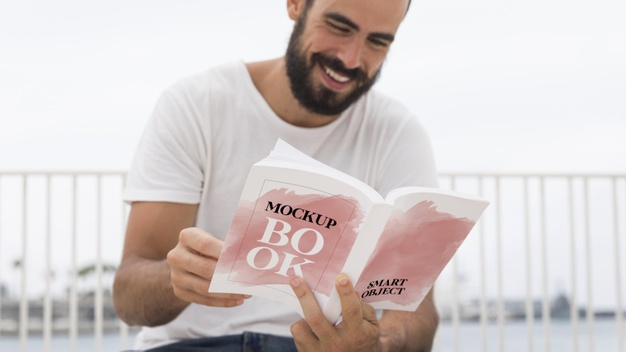 Man Smiling While Reading Book