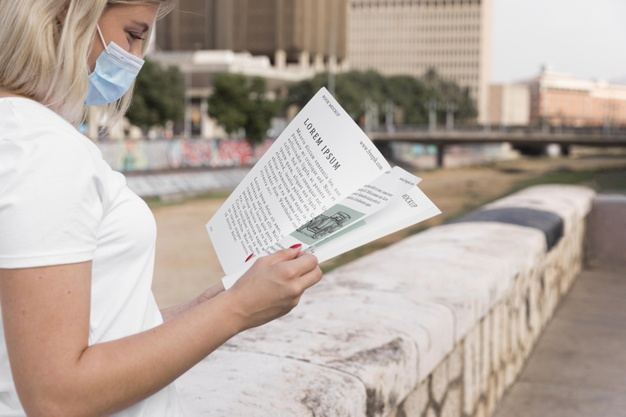 Woman with Mask Reading a Book on Street