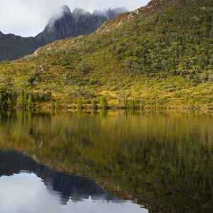Early morning reflections of a misty Cradle Mountain on Lake Lilla as sun bursts through the low lying cloud to highlight the shoreline.