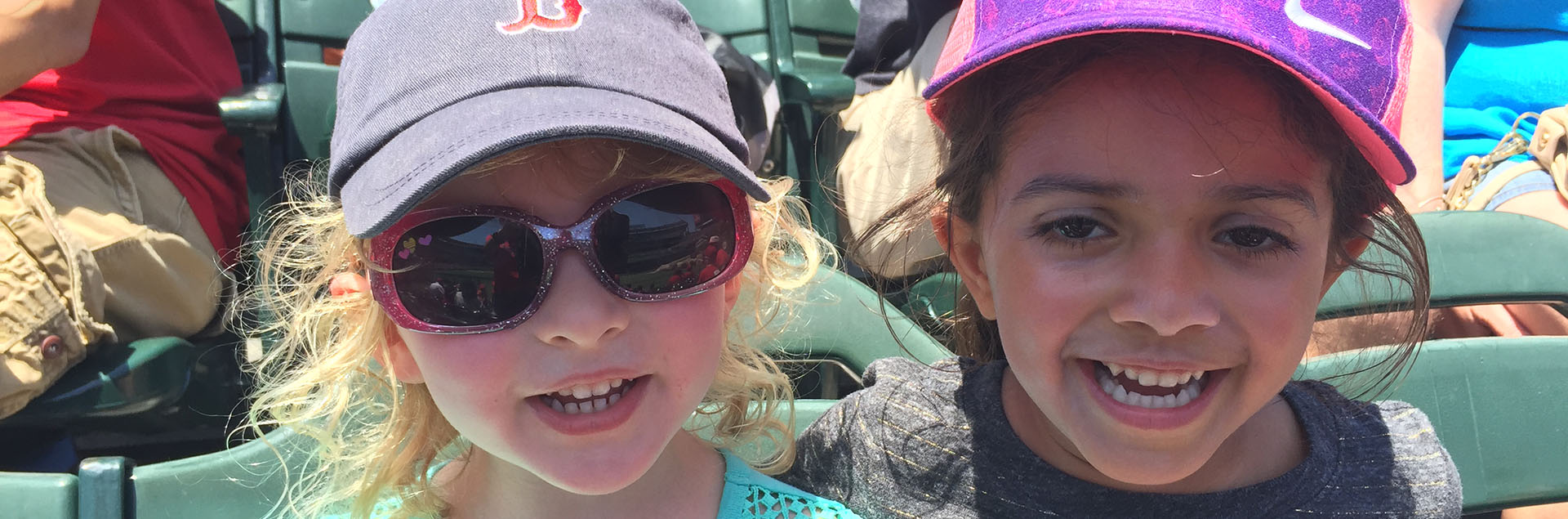 Little girls in stands at baseball game