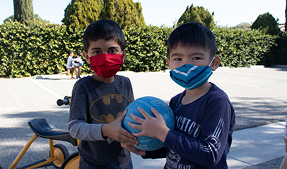 Little Boys with masks playing ball