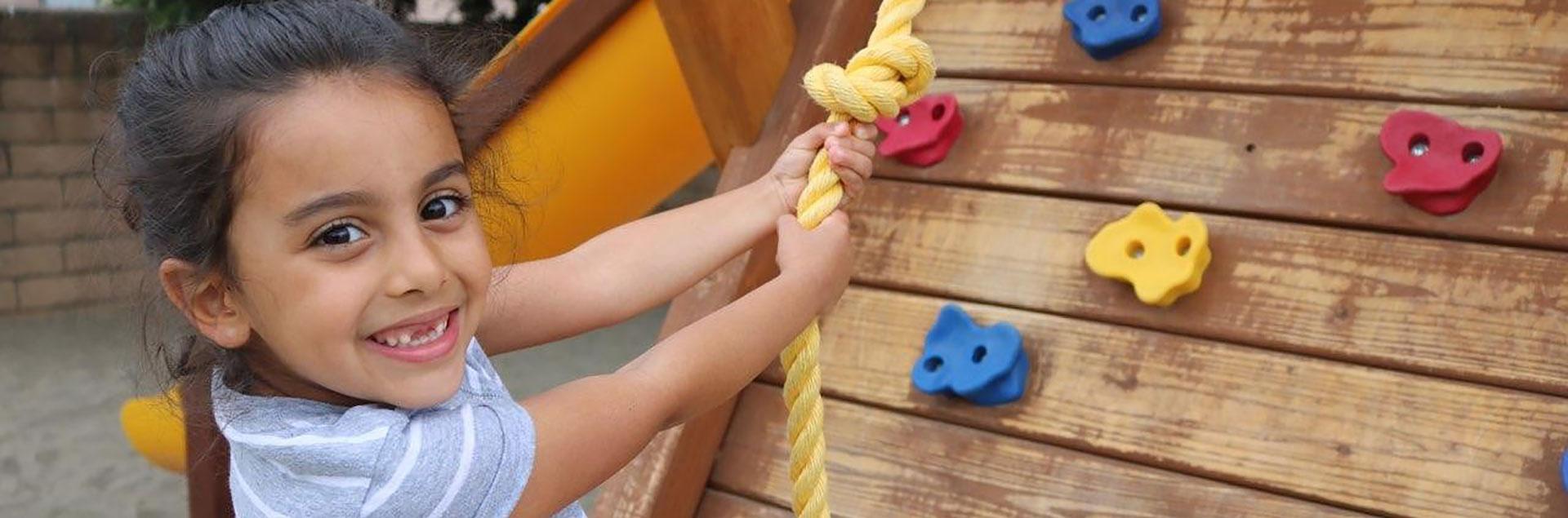 Girl climbing playground wall