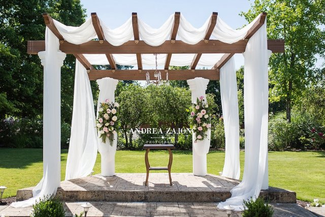 The Water Oasis Arbor draped with white chiffon, a chandelier and hanging flower baskets.