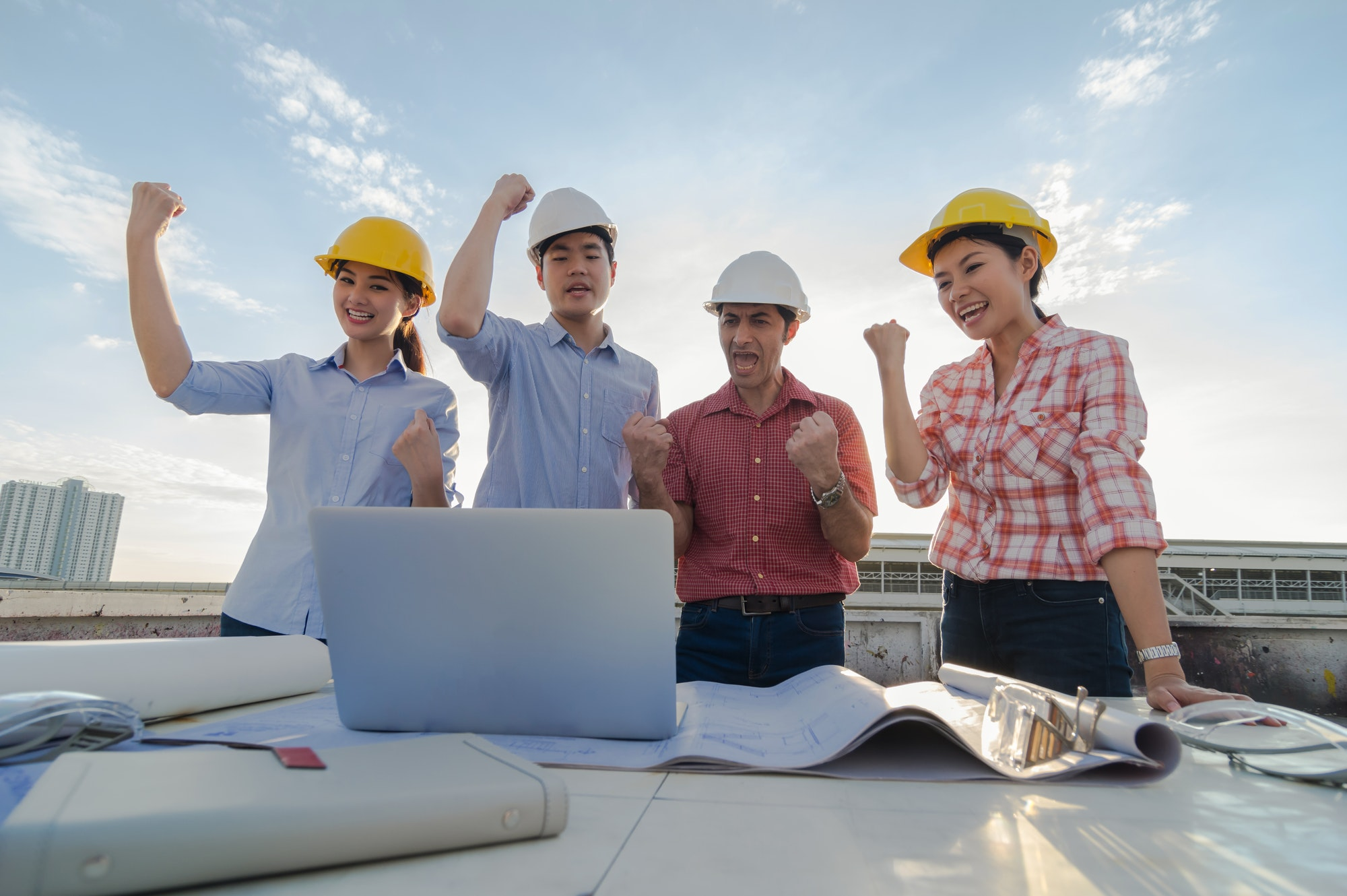 Happy professional construction engineers working in congratulation action after completed