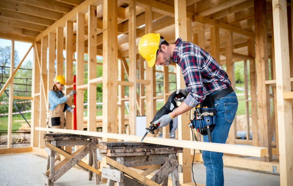 Team of workers doing woodwork at construction site of wood frame house
