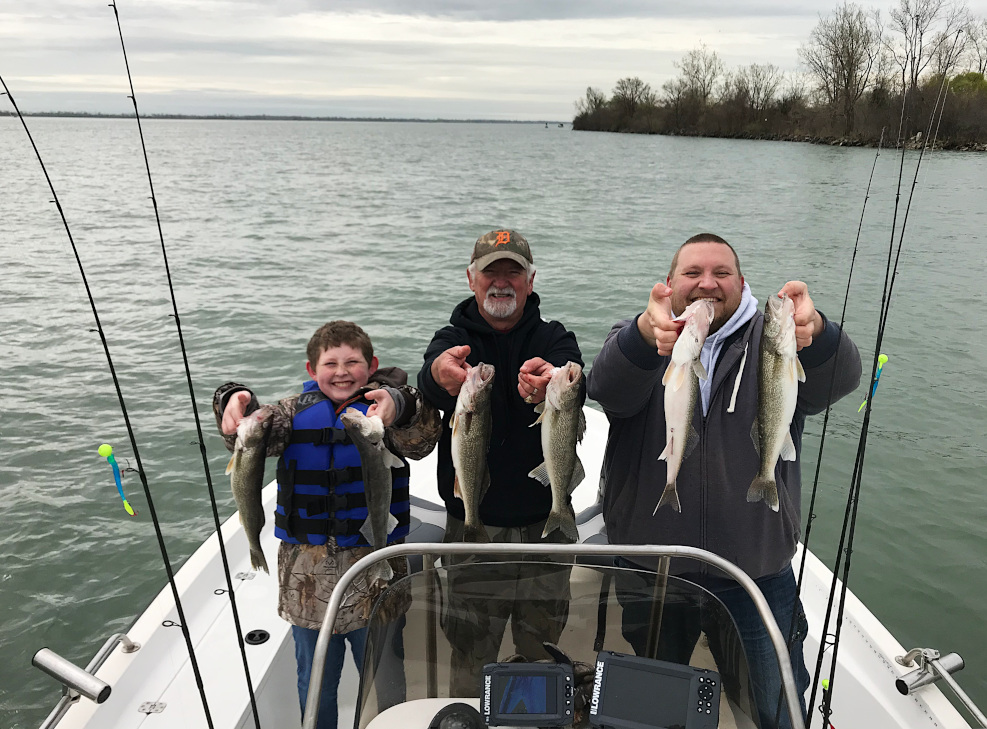 Family holding walleye on a Detroit River waleeye charter