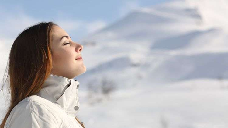 Woman Breathing Fresh Air on Mountain Top
