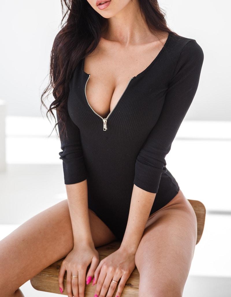 Beautiful brunette sitting in a chair wearing a black bodysuit