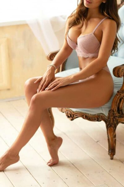 Busty Escort Scarlett sitting in a blue chair wearing sexy lingerie