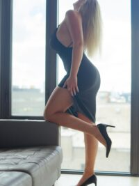 Blonde escort Blake wearing a black transparent dress
