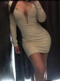 Toronto escort Mia taking a selfie wearing a tight white dress