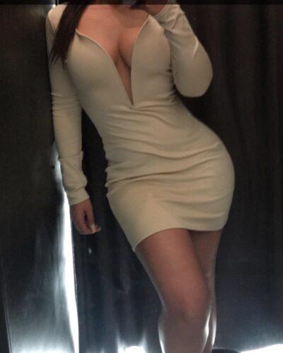 Toronto escort Mia taking a selfie wearing a tight white dress