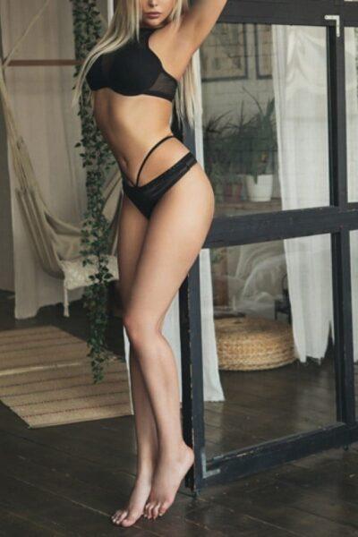 Beautiful Toronto escort standing by a door in lingerie