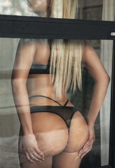 Sexy Blonde Escort sitting by window in lingerie